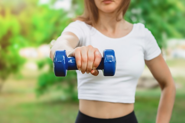 Sport training concept. female hand is holding a blue dumbbell