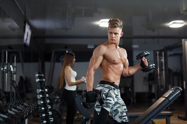 スポーツ、トレーニング、フィットネス、ライフスタイル、人々のコンセプト-パーソナルトレーナーが背中を曲げ、ジムのベンチで腹筋を持っている若い女性。高品質の写真