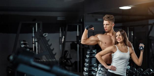 Спорт, обучение, фитнес, образ жизни и люди концепции - молодая женщина с личным тренером, сгибающим мышцы спины и живота на скамейке в тренажерном зале.
