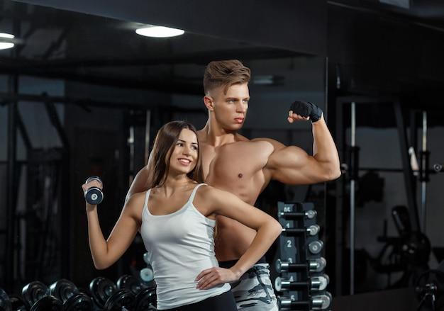 스포츠, 훈련, 피트니스, 라이프 스타일과 사람들 개념-체육관에서 벤치에 개인 트레이너 flexing 다시와 복부 근육을 가진 젊은 여자