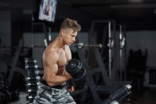 Sport, training, fitness, lifestyle and people concept - young woman with personal trainer flexing back and abdominal muscles on bench in gym. high quality photo