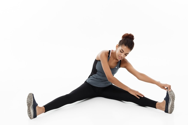 スポーツ、トレーニング、ライフスタイル、フィットネスのコンセプト-座っている間脚を伸ばしている幸せなアフリカ系アメリカ人女性の肖像画。白で隔離。