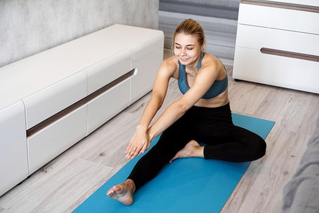 Sport, training and lifestyle concept - woman stretching leg on blue yoga mat at home in the living room