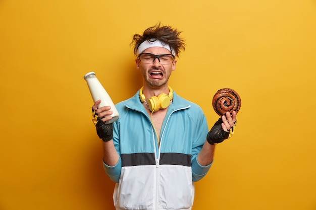 스포츠, 체중 감소 및 유혹 개념. 운동복을 입은 정서적 불쾌한 남자, 우유 병과 맛있는 달콤한 롤빵을 들고, 설탕 중독이 있으며, 건강하고 건강하게 유지하기 위해 스포츠에 참여합니다.