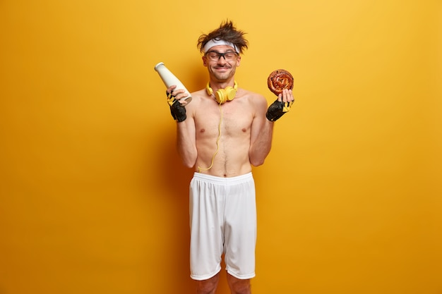 Sport and weight loss concept. positive sportsman has temptation to eat bun with milk, breaks diet, feels hungry after exercising in gym, wears sports clothes, isolated over yellow wall