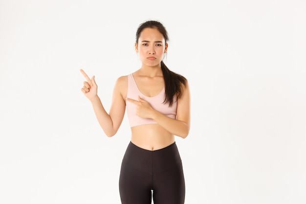 Sport, wellbeing and active lifestyle concept. complaining sad asian girl in activewear, sulking and frowning upset as pointing upper left corner, end of sale offer, standing white wall.
