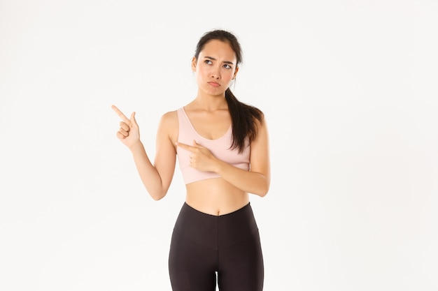 Sport, wellbeing and active lifestyle concept. complaining sad asian girl in activewear, sulking and frowning upset as pointing upper left corner, end of sale offer, standing white wall
