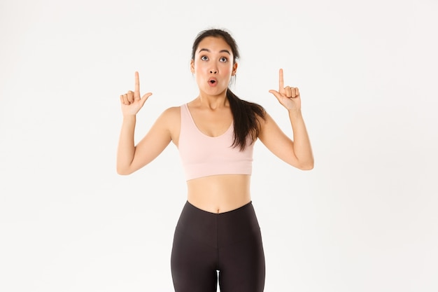 Sport, wellbeing and active lifestyle concept. excited and happy asian fitness girl in sportswear, pointing fingers up and looking amazed with great discounts, white wall