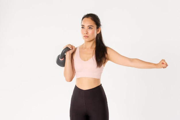 Sport, wellbeing and active lifestyle concept. focused and motivated asian female workout with kettlebell, lift weight and extend one hand, repeat exercise after coach in gym, white wall