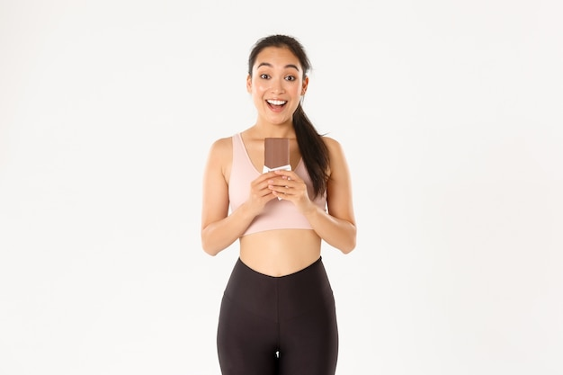 Sport, wellbeing and active lifestyle concept. happy smiling asian female athlete holding chocolate protein bad and looking excited, eating healthy sweets for prolonged workout.
