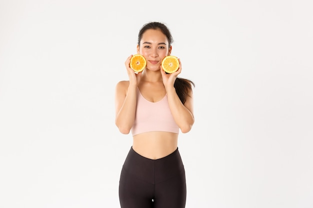 Sport, wellbeing and active lifestyle concept. silly and cute asian fitness girl, female athlete losing weight with workout, gym trainings and healthy diet, showing two halves of orange.