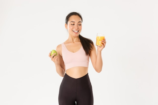 Sport, wellbeing and active lifestyle concept. smiling happy asian fitness girl in sportswear looking at orange juice pleased, eating apple after productive workout in gym, white background