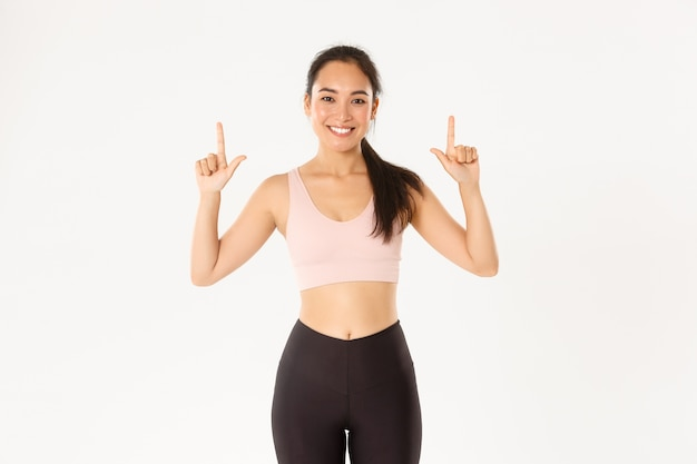 Sport, wellbeing and active lifestyle concept. smiling slim and cute asian fitness girl, female athlete pointing fingers up, showing workout equipment sale promo or gym membership offer.