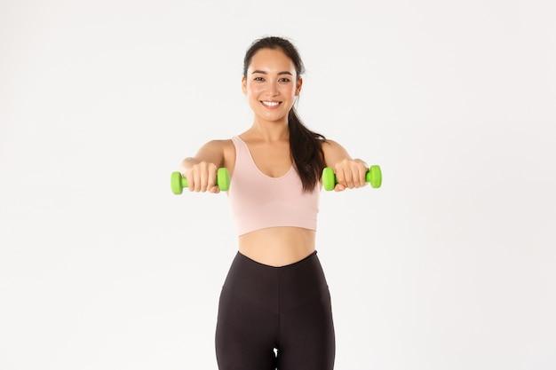 スポーツ、幸福、アクティブなライフスタイルのコンセプト。陽気な笑顔のアジアのフィットネスの女の子、ダンベルを持ち上げるスポーツウーマン、筋肉のトレーニング、ホームエクササイズで上腕二頭筋を取得、白い背景。