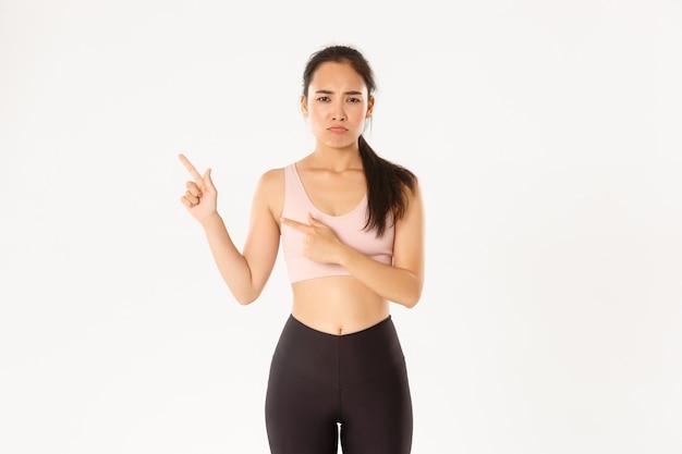 Концепция спорта, благополучия и активного образа жизни. жалуется на грустную азиатскую девушку в спортивной одежде, надуется и хмурится, когда она указывает на верхний левый угол, конец предложения, стоит белая стена.