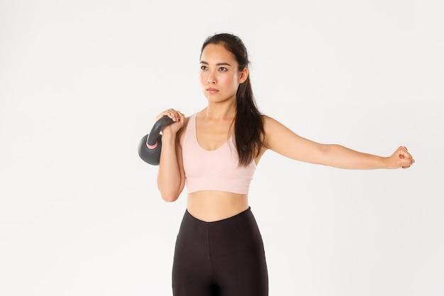 スポーツ、健康、アクティブなライフスタイルのコンセプト。ケトルベルで集中してやる気のあるアジアの女性のワークアウト、体重を持ち上げて片手を伸ばし、ジム、白い壁でコーチの後に運動を繰り返す