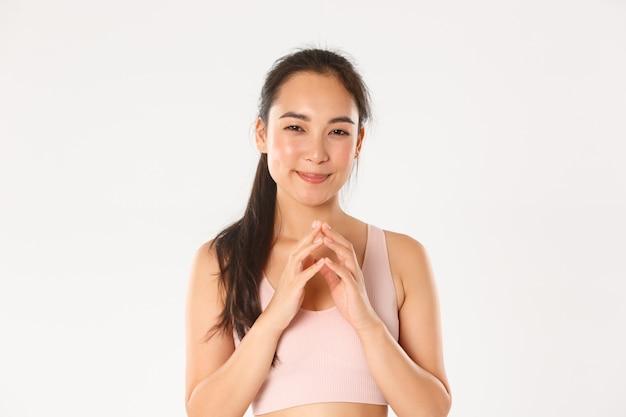 スポーツ、幸福、アクティブなライフスタイルのコンセプト。陰謀を企む思慮深いアジアのフィットネスの女の子、悪意のある計画を持っているスポーツウーマン、狡猾な笑顔と尖塔の指、立っている白い背景の肖像画。