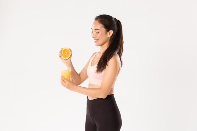 スポーツ、健康、アクティブなライフスタイルのコンセプト。笑顔の健康でスリムなアジアの女の子のアドバイス朝食に健康的な食べ物を食べる、良い運動のためにエネルギーを得る、ガラスにオレンジジュースを絞る