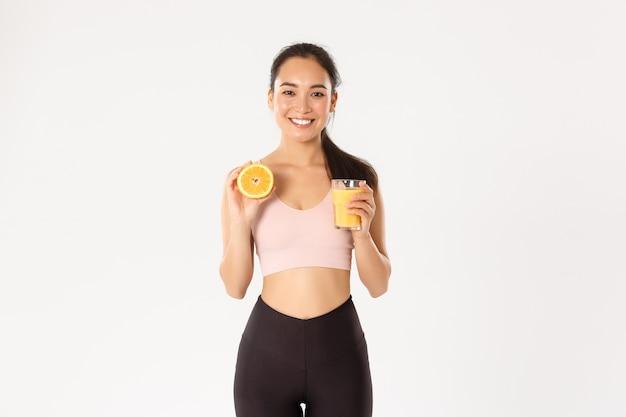 スポーツ、健康、アクティブなライフスタイルのコンセプト。朝食に健康的な食べ物を食べて健康的でスリムなアジアの女の子の笑顔の肖像画、トレーニングのエネルギーを得て、フレッシュジュースとオレンジを保持