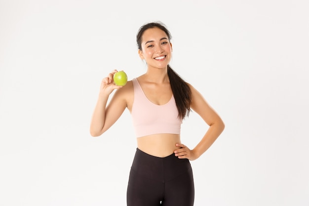 スポーツ、幸福、アクティブなライフスタイルのコンセプト。生意気な魅力的なアジアの女性フィットネスコーチ、アクティブウェアのアドバイスの女の子トレーナーは、リンゴと一緒に立って、トレーニングとトレーニングの後に健康的な食事を食べます。