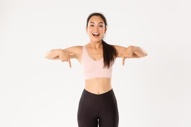 스포츠, 웰빙 및 활동적인 라이프 스타일 개념. 활력이 넘치는 아시아 피트니스 소녀, 이벤트에 초대하는 여성 운동 선수, 운동 장비 광고 표시, 손가락을 아래로 가리키는 미소,
