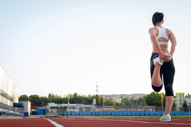 Sport and wellness. fitness girl in white sneakers doing stretching workout. fashion sporty woman with strong muscular body training. fit female stretching at outdoor stadium