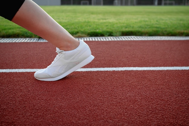 Sport and wellness. sportswoman practicing jogging in the stadium outside. close-up of a female leg in white sneakers. sports shoes for running. copy space