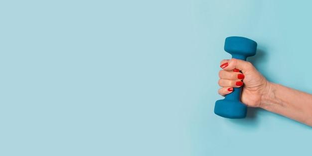 Женская рука с синей гантелью на синем sport wellness