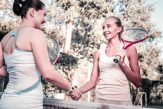 友達とスポーツ。テニスセットと握手をしている陽気な2人の女性のローアングル