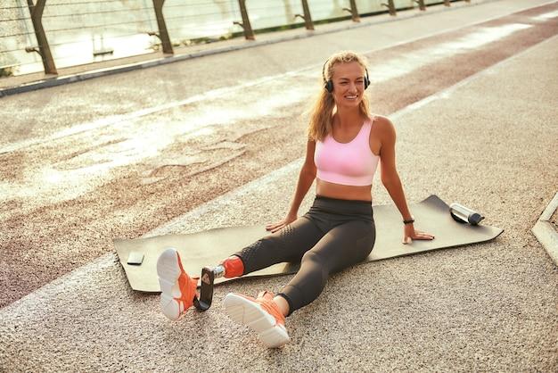 Спорт с музыкой позитивная женщина-спортсмен-инвалид с протезом ноги в наушниках, слушающая музыку