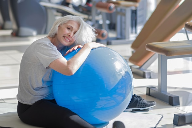 Спорт с удовольствием. веселая красивая женщина улыбается и обнимает подходящий мяч, делая упражнения в тренажерном зале.