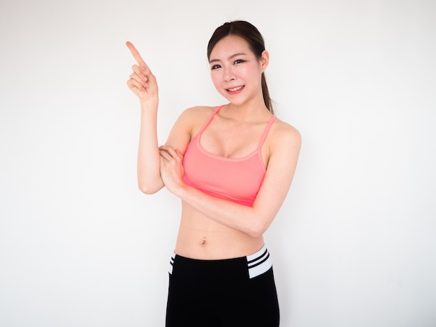 Sport woman arm cross with pointing finger up and smile,fitness concept