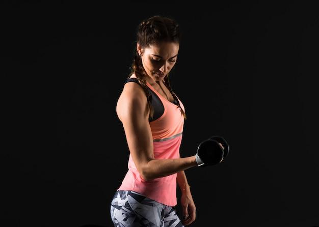 Sport woman on dark background making weightlifting