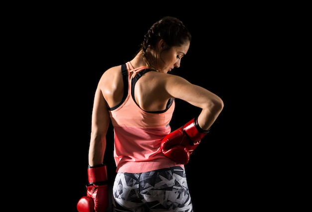 Sport woman on dark background with boxing gloves