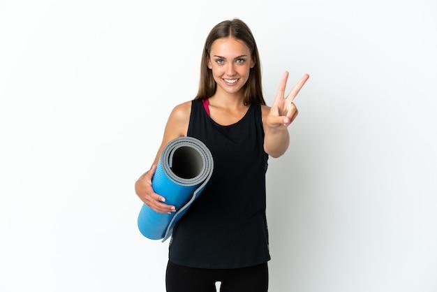 分離されたマットを押しながらヨガのクラスに行くスポーツ女性