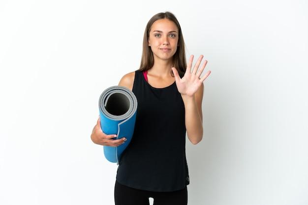 손가락으로 5를 세는 격리 된 흰색 배경 위에 매트를 들고 요가 수업에가는 스포츠 여자