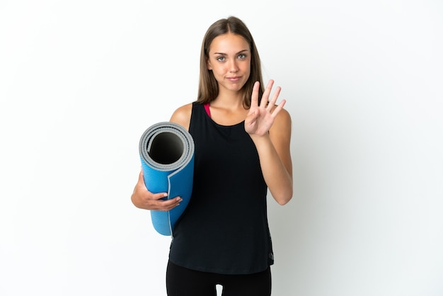 幸せな孤立した白い背景の上にマットを保持し、指で4を数えながらヨガのクラスに行くスポーツの女性