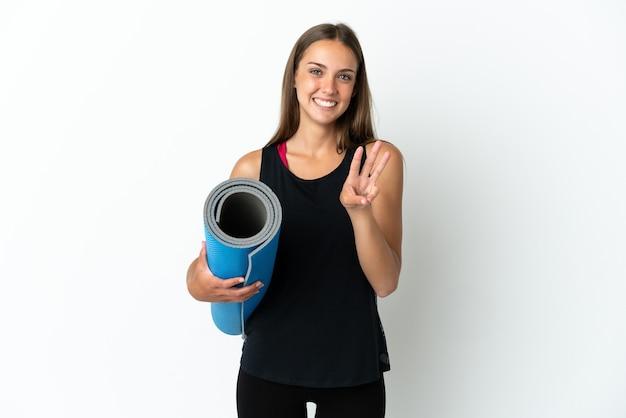 격리 된 흰색 배경 위에 매트를 잡고 손가락으로 세 세는 동안 요가 수업에가는 스포츠 여자