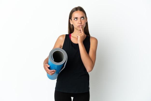 찾는 동안 의심을 갖는 고립 된 흰색 배경 위에 매트를 들고 요가 수업에가는 스포츠 여자