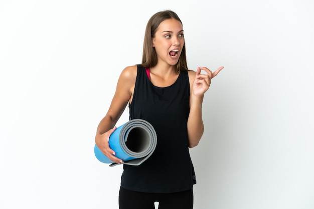 손가락을 들어 올리는 동안 솔루션을 실현하려는 격리 된 흰색 배경 위에 매트를 들고 요가 수업에가는 스포츠 여자