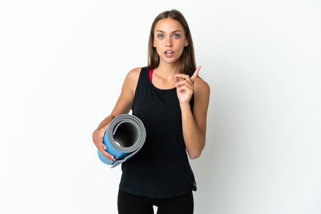 指を持ち上げながら解決策を実現することを意図して孤立した白い背景の上にマットを保持しながらヨガのクラスに行くスポーツの女性