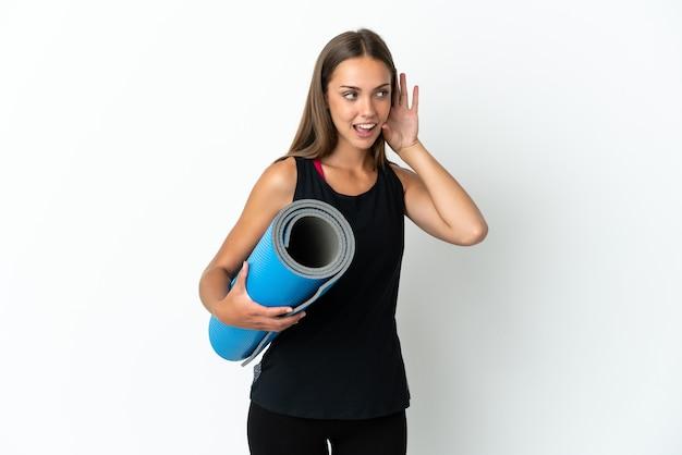 귀에 손을 넣어 뭔가를 듣고 격리 된 흰색 배경 위에 매트를 잡고 요가 수업에가는 스포츠 여자