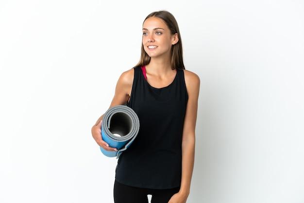 横を向いて笑顔で孤立した白い背景の上にマットを保持しながらヨガのクラスに行くスポーツの女性