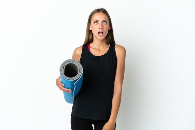 격리 된 흰색 배경 위에 매트를 들고 놀란 표정으로 요가 수업에가는 스포츠 여자