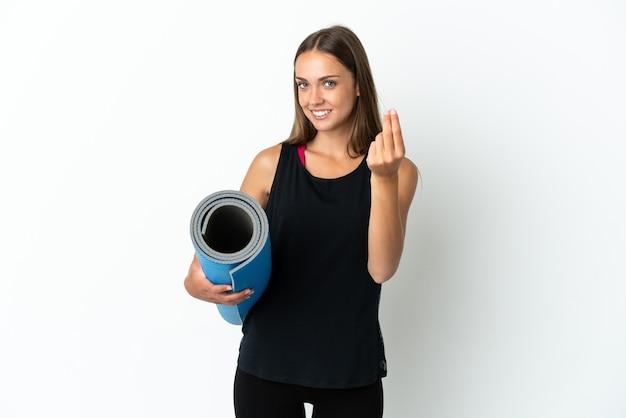 Спортивная женщина собирается на занятия йогой, держа циновку на изолированном белом фоне, делая денежный жест