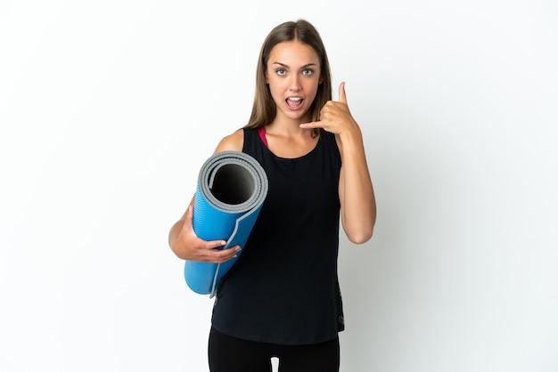 電話のジェスチャーを作る孤立した白い背景の上にマットを保持しながらヨガのクラスに行くスポーツの女性。コールバックサイン