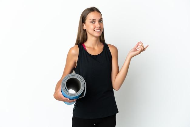 측면에 손가락을 가리키는 격리 된 흰색 배경 위에 매트를 잡고 요가 수업에가는 스포츠 여자