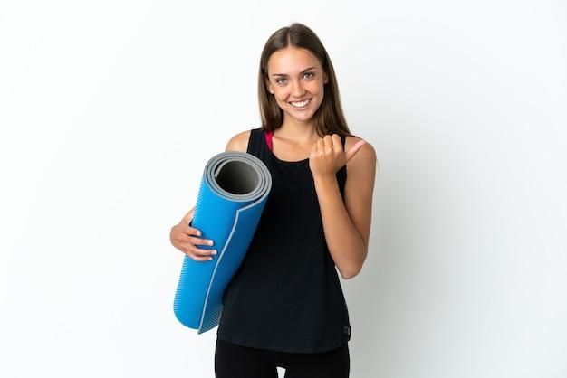 製品を提示する側を指している孤立した白い背景の上にマットを保持しながらヨガのクラスに行くスポーツの女性
