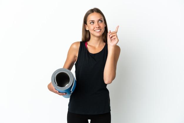 素晴らしいアイデアを指している孤立した白い背景の上にマットを保持しながらヨガのクラスに行くスポーツの女性