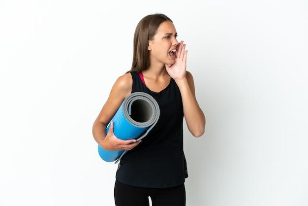 Спортивная женщина идет на занятия йогой, держа циновку на изолированном белом фоне, кричит с широко открытым ртом